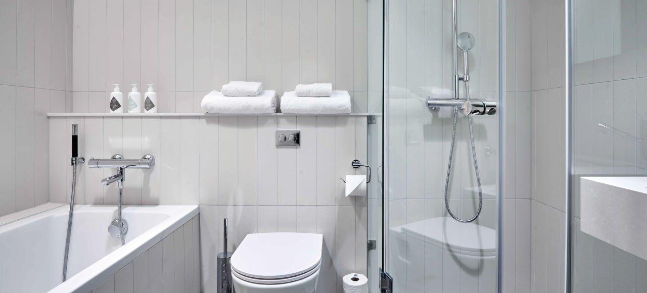 Helkaklat badrum med både dusch och bad på Nordic Light Hotel